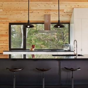 Nowoczesną atmosferę do przestrzeni kuchni wprowadza loftowe oświetlenie, połyskujący blat i podwieszany zlewozmywak, chowający się w blacie. Projekt: MU Architecture. Fot. Ulysse Lemerise Bouchard.