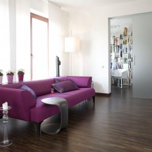 Śliwkowa sofa to zdecydowanie najmocniejszy detal w aranżacji niewielkiego salonu. Pokój wypoczynkowy graniczy z gabinetem, ukrytym za przesuwanymi drzwiami. Projekt: Małgorzata Szajbel-Żukowska, Maria Żychiewicz. Fot. Marcin Onufryjuk.