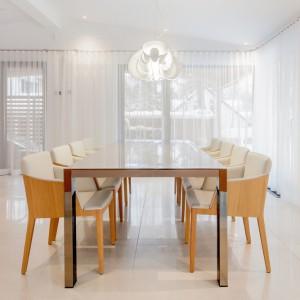 W jadalni królują jasne barwy. Ściany i firany w dużych oknach są białe, podłoga ma delikatny odcień ecru, biała jest również lampa nad stołem. Na tle tak subtelnych odcieni, stół jadalniany i krzesła stają się mocno wyeksponowane, mimo, że same również zostały utrzymane w stonowanych barwach. Projekt: Frédric Clairoux, Julie Lafontaine. Fot. JB Valiquette.