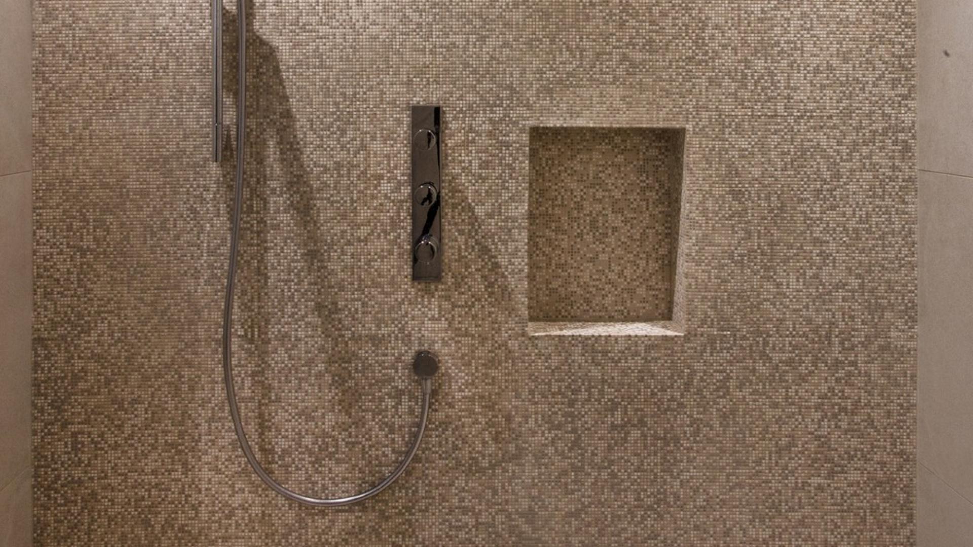 Strefę prysznica utrzymano w kolorze kawy z mlekiem. Minimalizm form został tutaj przełamany przez piaskową fakturę ścian i podłogi. Projekt: Frédric Clairoux, Julie Lafontaine. Fot. JB Valiquette.