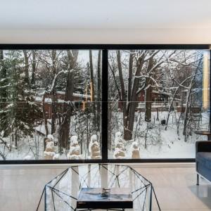 Panoramiczne przeszklenia oprawiono w ciemne ramy, wyeksponowane na tle białych ścian. Projekt: Frédric Clairoux, Julie Lafontaine. Fot. JB Valiquette.