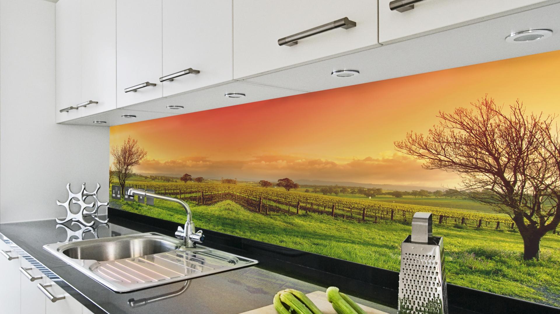 Soczyście zielona łąka, nad którą góruje pomarańczowe, wieczorne niebo, rozciąga się efektownie nad blatem kuchennym, wprowadzając akcent kolorystyczny do białej kuchni. Fot. DecoMania