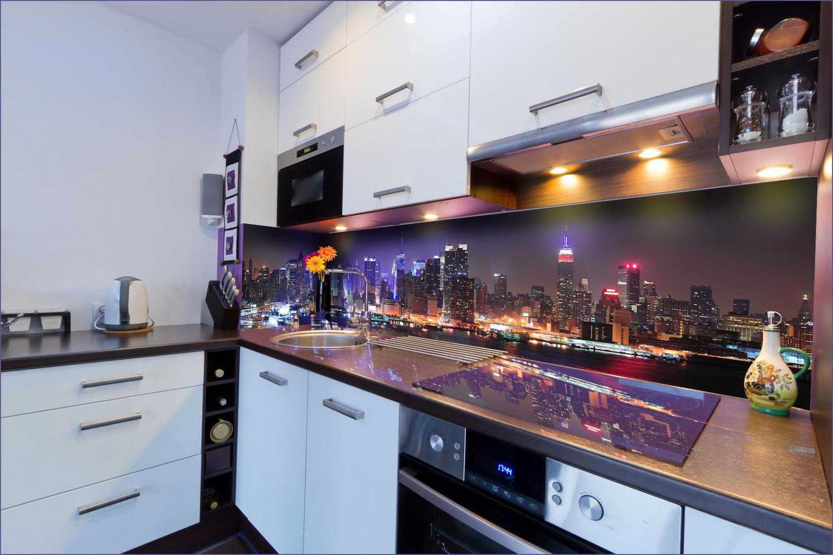 Krajobraz wielkiego miasta nocą efektownie odcina się od jasnych mebli kuchennych. Fot. Grafdeco.