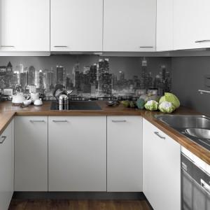 Nowy Jork w czerni i bieli zdobi ścianę nad blatem w tej kuchni, zdominowanej przez biel frontów mebli. Eleganckie, stonowane rozwiązanie. Fot. Big-Trix.