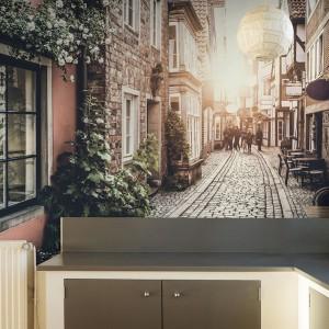 Ścianę nad blatem w kuchni zdobi piękna fototapeta, ukazująca romantyczną wąską uliczkę. Daleka perspektywa na zdjęciu optycznie powiększa wnętrze, dodając mu głębi. Fot. Big-Trix.