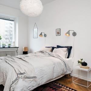 Delikatne kinkiety umieszczone nad łóżkiem dostarczają odpowiednią ilość światła. Są także subtelnym elementem dekoracyjnym. Fot. Alvhem Makleri.