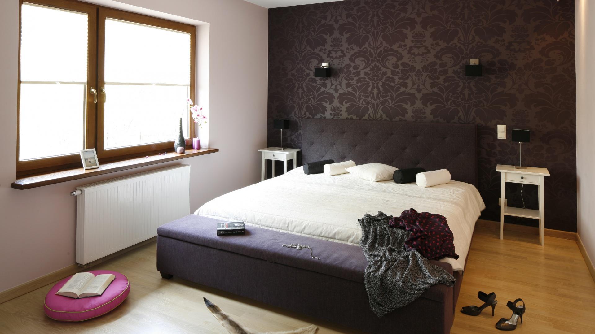Tapicerowane łóżko z wysokim, pikowanym zagłówkiem efektownie prezentuje się na tle wzorzystej tapety. Projekt: Jolanta Kwilman. Fot. Bartosz Jarosz.
