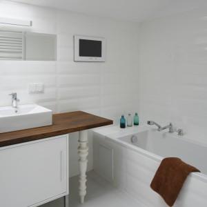 Z tej łazienki na poddaszu korzystają dorośli i dzieci, które w kąpieli chętnie oglądają bajki w telewizorze zawieszonym nad wanną. Aranżacja w bieli zapewnia łazience modny wygląd na lata. Projekt: Konrad Grodziński. Fot. Bartosz Jarosz.