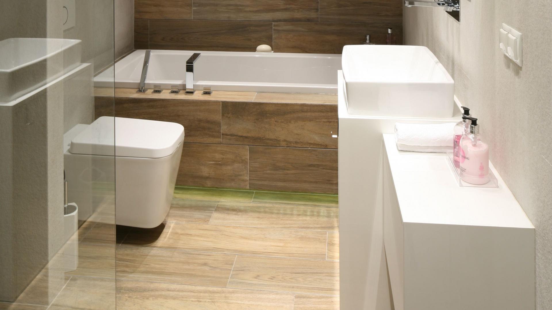 Łazienka jest nowoczesna i przytulna zarazem. To efekt zastosowania płytek ceramicznych o wzorze imitującym naturalne drewno. Projekt: Dominik Respondek. Fot. Bartosz Jarosz.
