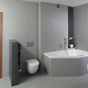 Łazienka dla rodziny urządzona jest w stylu minimalistycznym.  Do wykończenia podłóg i ścian  wybrano materiały w kilku odcieniach szarości. Projekt: Piotr Stanisz. Fot.  Bartosz Jarosz.