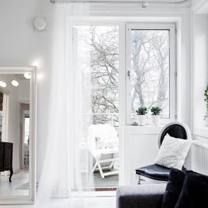 Duże lustro, ustawione obok drzwi balkonowych optycznie powiększa wnętrze. Ozdobione dekoracyjnym oświetleniem, przywodzi na myśl garderoby gwiazd estrady. Fot. Stadshem.se/Janne Olander.