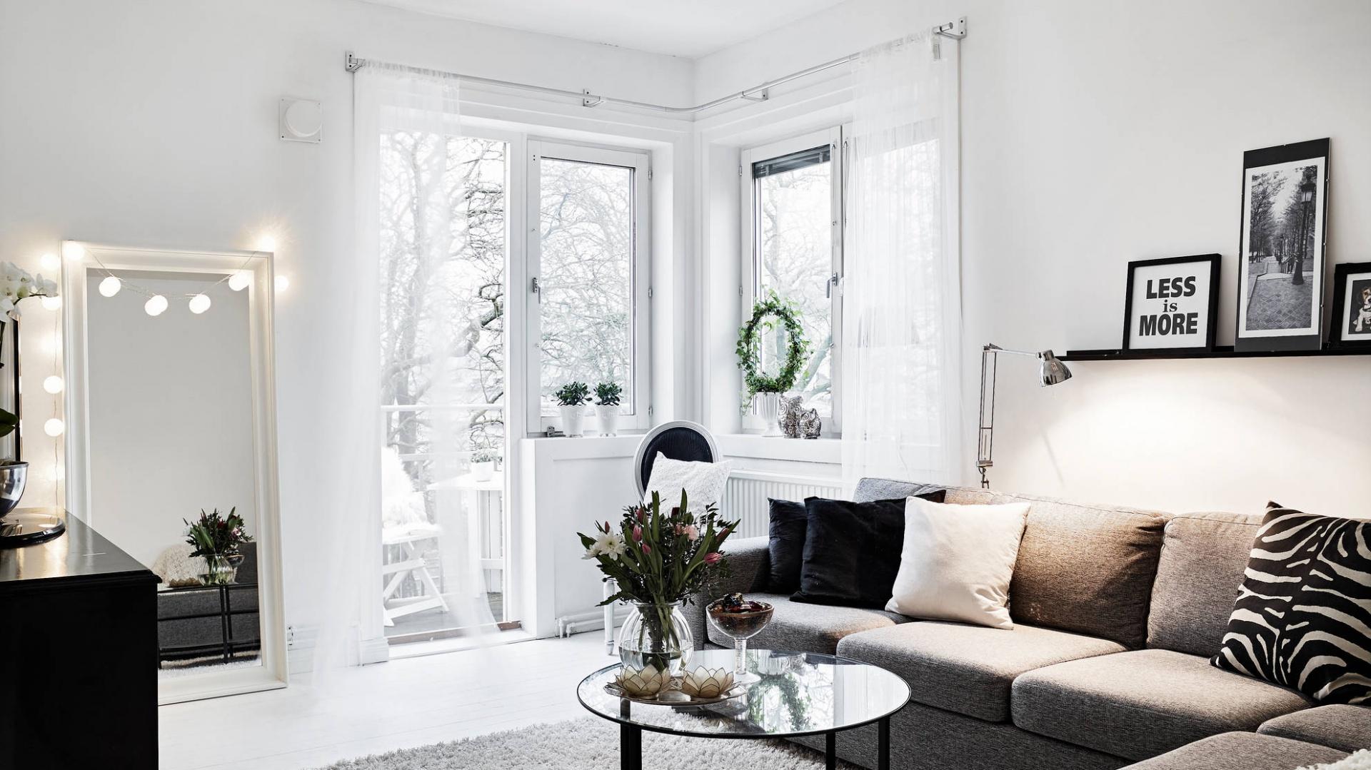 Narożne przeszklenia wpuszczają do wnętrza dużo naturalnego światła, które odbija się od jasnych ścian, rozświetlając i powiększając optycznie pomieszczenie. W salonie, sterylną biel przełamują czarne dodatki oraz duży, szary narożnik. Fot. Stadshem.se/Janne Olander.