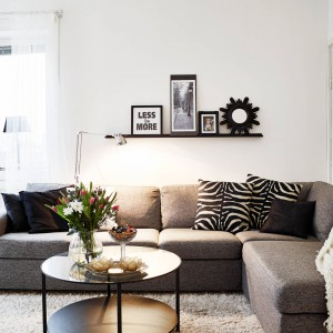 Przytulną atmosferę w salonie tworzą bogato użyte dekoracyjne tekstylia na narożniku oraz miękki, kosmaty dywan. Fot. Stadshem.se/Janne Olander.