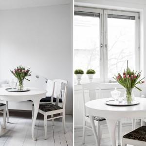 W kuchni wygospodarowano miejsce na jadalnię. Stół i krzesła mają lekko klasycyzujące, stylizowane formy, harmonizujące z dekoracyjnym żyrandolem. Fot. Stadshem.se/Janne Olander.
