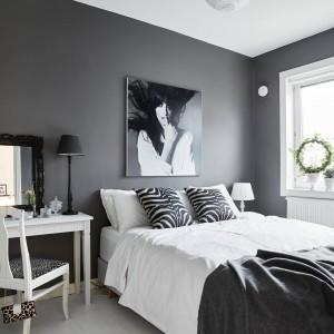 Na tle ciemnoszarych ścian w sypialni, pięknie wyeksponowano białe meble. Nad wezgłowiem łóżka - dekoracyjna fotografia, utrzymana w czerni i bieli. Fot. Stadshem.se/Janne Olander.