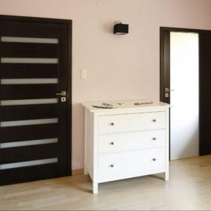 Między drzwiami ustawiono białą, pojemną komodę z trzema szufladami, która formą nawiązuje do stolików nocnych. Projekt: Jolanta Kwilman. Fot. Bartosz Jarosz.