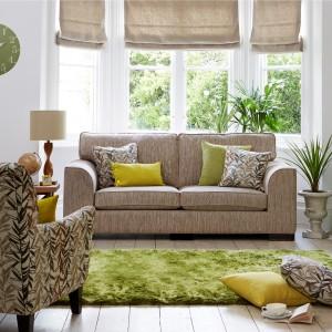 Pomysł na ożywienie salonu skąpanego w beżach. Poduszki dekoracyjne w odcieniach zieleni i żółci efektownie odmieniają aranżację. Efektu dopełnia dywan przypominający świeżą murawę. Fot. Furniture Village.