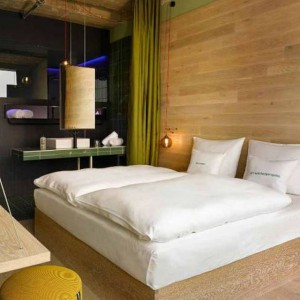 Naturalne drewno i spokojne odcienie zieleni tworzą spójną, harmonijną przestrzeń. Taki pokój oferuje hotel w Berllinie. Fot. 25 hours Hotels.