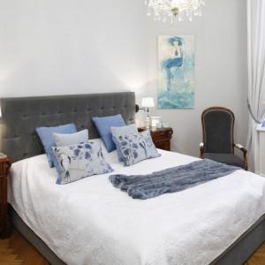 Romantyczną i elegancką sypialnię otulają różne odcienie szarości i błękitu. Łóżko zostało wykonane na zamówienie, zaś fotele i bieliźniarki zakupiono na targu staroci. Projekt: Iwona Kurkowska. Fot. Bartosz Jarosz.
