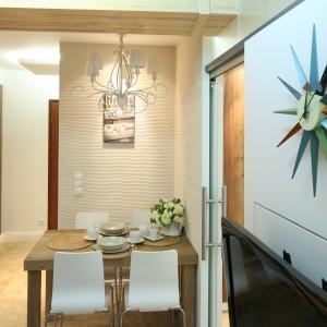 Biały żyrandol w stylu francuskim oświetla ten niewielki jadalniany stół, nadając wnętrzu elegancki charakter. Kolorystycznie, ramiona i klosze komponują się z krzesłami przy stole. Projekt: Łukasz Sabat. Fot. Bartosz Jarosz.