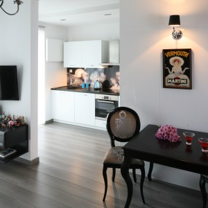 Stylizowany, nieduży stolik jadalniany harmonizuje z ciekawym rozwiązaniem oświetleniowym. Zamiast wiszącej lampy - montowany w ścianie kinkiet w czarnym kloszu, harmonizującym z kolorem mebli. Projekt: Joanna Nawrocka. Fot. Bartosz Jarosz.