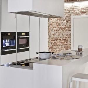 Czarne sprzęty AGD Miele, wbudowano w białą, wysoką zabudowę. Odnajdziemy tutaj piekarnik, kuchenkę, a także ekspres do kawy. Każdy sprzęt umiejscowiony w oddzielnym słupku, pozwala na bezkolizyjne korzystanie z poszczególnych urządzeń. Fot. Zajc Kuchnie.