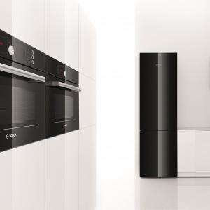 Piekarnik kompaktowy HBC86P763 ze zintegrowaną mikrofalą. Urządzenie, dzięki estetycznemu wzornictwu i barwie, efektownie wygląda na tle wysokiej, białej zabudowy. Czarne szkło zamiast stali szlachetnej, dodaje mu elegancji i czyni z niego pełnoprawny element wyposażenia kuchni. Fot. Bosch.