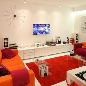W kolorowym i bardzo kobiecym salonie telewizor zawisł w centralnym miejscu na tle białej ściany, którą zdobi lekki w formie, pokaźnych rozmiarów zegar. Projekt: Katarzyna Mikulska-Sękalska. Fot. Bartosz Jarosz.