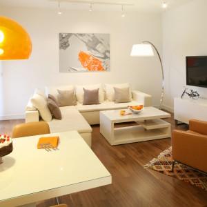 Nadmorski apartament urządzono w klasycznych bielach i beżach. Duży telewizor zawisł na jednej ze ścian, tuż nad nowoczesna szafką RTV. Narożna kanapa zapewnia wystarczająco dużo miejsca na rodzinne oglądanie telewizji. Projekt: Małgorzata Galewska. Fot. Bartosz Jarosz.