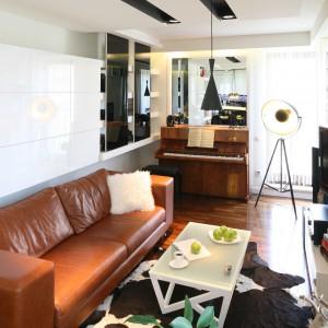 Nieduży salon w bloku urządzono w optycznie powiększającej przestrzeń bieli. Lustro tuż za pianinem oraz lakierowane w połysku meble dodatkowo potęgują ten efekt. Projekt: Małgorzata Mazur. Fot. Bartosz Jarosz.