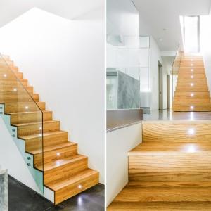Drewniane schody dywanowe wprowadzają do wnętrza element przytulności. Szklana balustrada i efektowne oświetlenie poszczególnych stopni nadają wnętrzu nowoczesny charakter. Projekt: MU Architecture. Fot. Ulysse Lemerise Bouchard.
