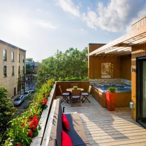 Pod zadaszeniem na tarasie, usytuowano jacuzzi, a po przeciwległej stronie komplet komfortowych mebli ogrodowych. Projekt: MU Architecture. Fot. Ulysse Lemerise Bouchard.
