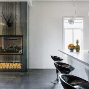 Na granicy salonu i kuchni znalazł się kominek w pięknej, stalowej oprawie. Chłodna w swoim wyrazie powierzchnia idealnie harmonizuje z betonową posadzka i blatem. Projekt: MU Architecture. Fot. Ulysse Lemerise Bouchard.
