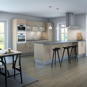 Aneks kuchenny i spory półwysep harmonizują z drewnianą podłogą, wprowadzając do wnętrza, zamkniętego w szare ściany, element ciepłego beżu. Fot. Nettoline, kuchnia Torino Ask.