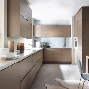 Gładkie, nowoczesne fronty w ciepłym, przytulnym kolorze drewna stanowią podstawę kolorystyczną tej kuchni. Skomponowano je z szarą ścianą i krzesłami. Fot. Black Red White, kuchnia Capital, kolekcja Senso Kitchens.