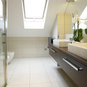 Dosyć wąską łazienkę pod skosem urządzono tak, że wpadające przez okno światło doskonale oświetla strefę umywalek oraz lustro nad nimi. Projekt: Magdalena Wielgus-Biały. Fot. Bartosz Jarosz.