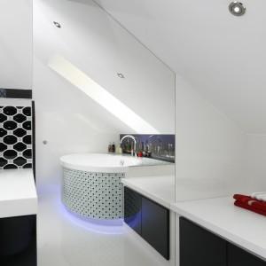 Lustro na ścianie to pomysł na optyczne powiększenie łazienki. Odbija się w nim także skos dachowy.  Projekt: Marta Kilan. Fot. Bartosz Jarosz.