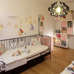 Największą dekoracją pokoiku jest jednak unikatowe, kute ręcznie łóżko. Kolorowe sny przynoszą zaś dziecku długowłose wróżki, zdobiące ścianę. Na niej też zainstalowano geometryczny kinkiet, umożliwiający dziecku czytanie bajek przed snem. Takie samo oświetlenie występuje też nad biurkiem, na którym Marysia tworzy soje malunki. Fot. Archiwum Dobrze Mieszkaj.