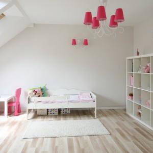Biały, całkiem sporych rozmiarów pokój na poddaszu, za sprawą małych mebelków stał się cukierkową krainą zabawy dla kilkuletniej dziewczynki. Jasnej, pudrowej aranżacji wnętrza,  dziewczęcy charakter nadają detale w kolorze dojrzałych malin: krzesełka oraz abażury kinkietu i żyrandola. Różową barwę wnoszą do wnętrza także przedmioty codziennego użytku: książki, maskotki czy pościel. Projekt: Karolina i Artur Urban. Fot. Bartosz Jarosz.