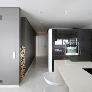 Długa ścianka działowa pomiędzy klatką schodową i salonem, delikatnie odgradza pokój dzienny od przestrzeni kuchni. Projekt: Ramunas Manikas, Valdas Kontrimas. Fot. Ramunas Manikas.