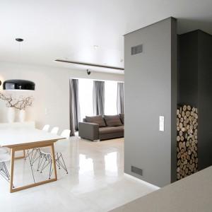 Ciekawym rozwiązaniem jest składzik na drewno opałowe, usytuowany w zabudowie. Oprócz praktycznej funkcji, ułożone drewno ociepla także wizualnie chłodny wystrój wnętrza. Projekt: Ramunas Manikas, Valdas Kontrimas. Fot. Ramunas Manikas.