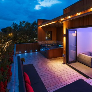 Relaksowi na powietrzu sprzyja nastrojowe oświetlenie i dekoracyjne rośliny. A gdy zrobi się chłodno, wieczorem można się skryć wewnątrz mieszkania, podziwiając wieczorną panoramę miasta przez panoramiczne przeszklenia. Projekt: MU Architecture. Fot. Ulysse Lemerise Bouchard.