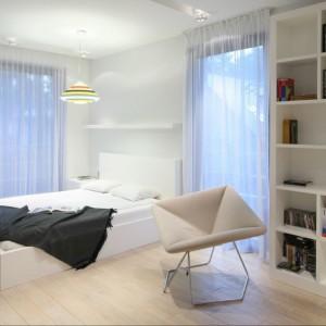 W sypialni urządzonej w nowczesnym stylu dominują proste formy mebli. Kolor wprowadza wisząca lampa oraz elementy umieszczone wewnątrz białej, wysokiej zabudowy. Projekt: Nasciturus design. Fot. Bartosz Jarosz.