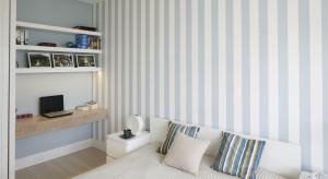 W tej sypialni biel połączono z delikatnym błękitem. Całość ocieplono jasnym drewnem, tworząc wyjątkowo przytulne, spokojne wnętrze.