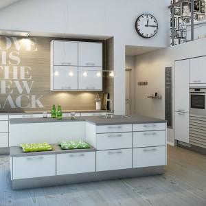 Białe meble kuchenne z funkcjonalnymi, długimi uchwytami to wygoda w korzystaniu z kuchni. Drewniana podłoga, dopasowany kolorystycznie blat oraz ściana nad nim w kolorze drewna, wprowadzają do wnętrza element skandynawskiej stylistyki. Fot. Nettoline, model Dab Elegant i Stecca.