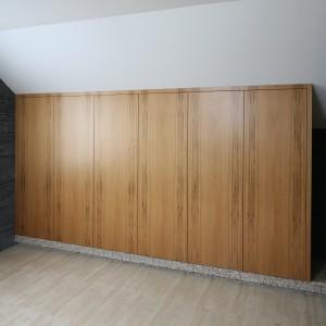 Szafa zajmuje prawie cała ścianę i oferują na tyle dużo miejsc do przechowywania, że właściciele urządzili w tej części łazienki swoją garderobę. Projekt:  Karolina Łuczyńska. Fot. Bartosz Jarosz.