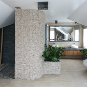 W przestronnym salonie kąpielowym znajduje się praktyczna komoda, m.in. z koszem na pranie. Po przeciwnej stronie miejsce pod skosem wykorzystane zostało na szafy. Projekt:  Karolina Łuczyńska. Fot. Bartosz Jarosz.