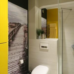 Widoczna w lustrze szafa wykonana z MDF-u lakierowanego na słoneczny, żółty kolor nie tylko dodaje energii łazience, ale jest niezwykle pojemna i praktyczna. Projekt: Dorota Szafrańska. Fot. Bartosz Jarosz.