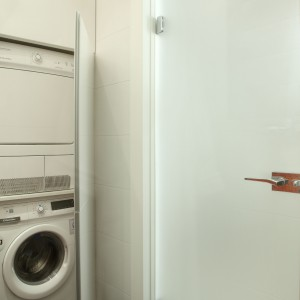 Jeden z segmentów przeznaczono na pralkę oraz suszarkę, na co dzień schowane za meblowymi drzwiami. Projekt: Michał Mikołajczak. Fot. Monika Filipiuk-Obałek.