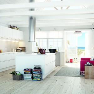 Białe meble kuchenne w nowoczesnym stylu wkomponowano w przestronne, jasne pomieszczenie z wyeksponowanymi belkami stropowymi, pomalowanymi na biało. Dominację bieli przełamuje drewniana podłoga. Fot. HTH, model Glat Hvid.